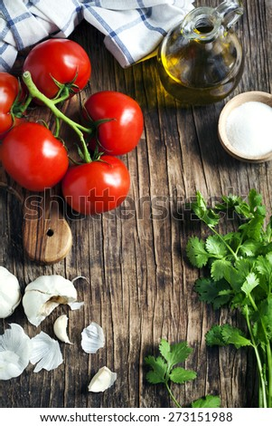 Fresh tomatoes, garlic and cilantro on wooden background