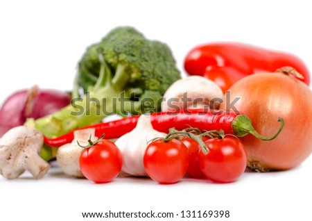 Fresh tomatoes, garlic and red hot chilli pepper to be used as flavouring ingredients in cooking in front of a selection of assorted farm vegetables with shallow dof on a white background - stock photo