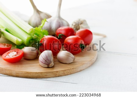 Fresh tomatoes, garlic and stems of celery on cutting board on white wooden background. Copyspace - stock photo