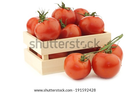 fresh tomatoes in a wooden box on a white background