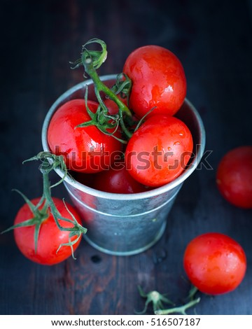 Fresh tomatoes in metal bucket on wooden background. Rustic style. country style. Dew on tomatoes. Tomatoes on a branch
