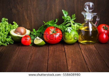 Fresh tomatoes, lime, avocado, lettuce, parsley and olive oil on dark wood background with space for text. Healthy food. Vegetables and greens. Salad ingredients.