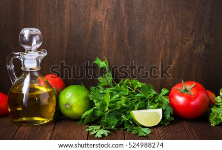 Fresh tomatoes, lime, lettuce, parsley and olive oil on dark wood background with space for text. Healthy food. Vegetables and greens. Salad ingredients.