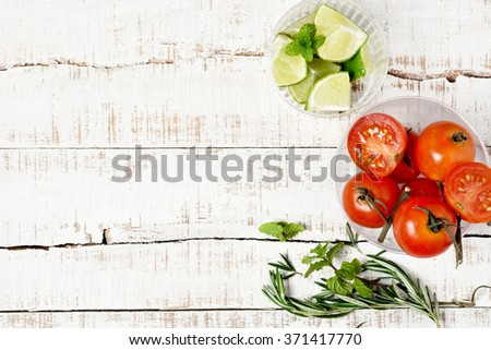 fresh tomatoes, limes and herbs on old wooden table. Ingredients for food and drinks. detox, juice, smoothie