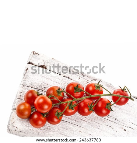fresh tomatoes on a branch of cherry varieties lie on a wooden board  isolated on white background - stock photo