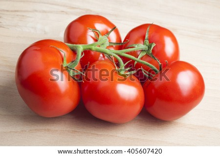 Fresh tomatoes over wooden background - stock photo