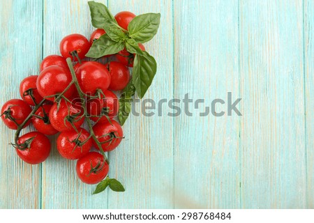 Fresh tomatoes with basil on wooden background - stock photo