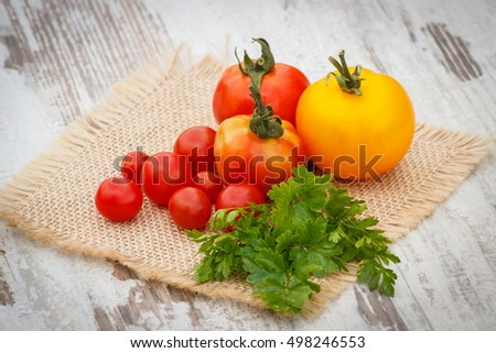 Fresh tomatoes with green leaves on jute canvas on old white wooden table in garden on sunny day, healthy nutrition