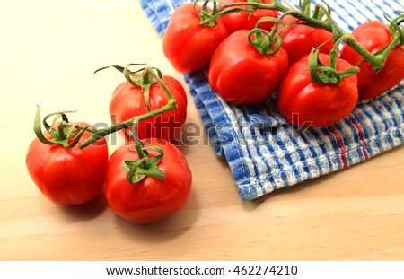 Fresh tomatoes with green leaves over wooden table background