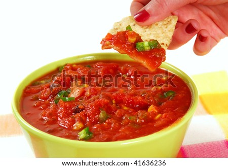Fresh tortilla chip being dipped into a hot and spicy salsa - stock photo