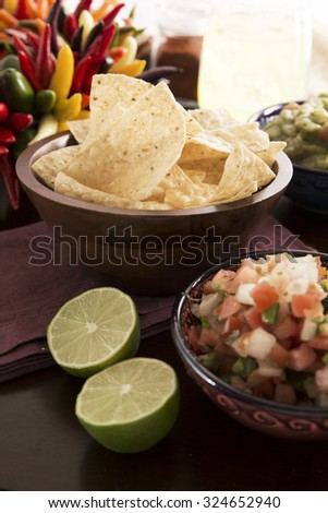 Fresh tortilla chips with pico de gallo and fresh limes in forground, guacamole and a margaritia in the background. - stock photo