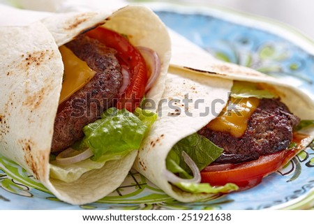 Fresh tortilla wrap with grilled beef burger and vegetables