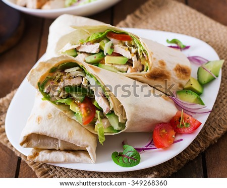 Fresh tortilla wraps with chicken and fresh vegetables on plate - stock photo