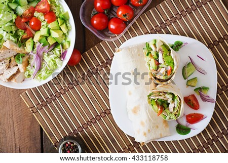 Fresh tortilla wraps with chicken and fresh vegetables on plate. Top view - stock photo