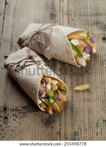 Fresh tortilla wraps with grilled chicken,vegetables and potato, selective focus - stock photo