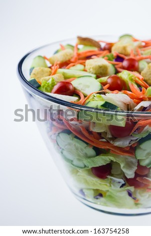 Fresh tossed garden salad in a glass bowl set against a white background. - stock photo