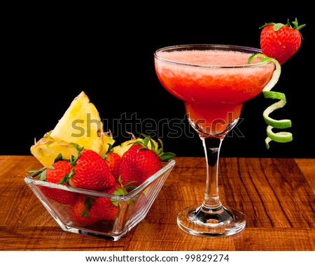 fresh tropical fruit cocktail on a bar top isolated on a black background - stock photo