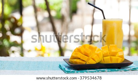 Fresh tropical fruit smoothie mango juice and fresh mango on a outdoor tropical background Copy space - stock photo