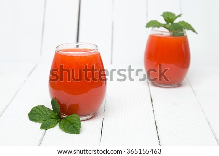 Fresh tropical papaya juice isolated on a white wooden background.