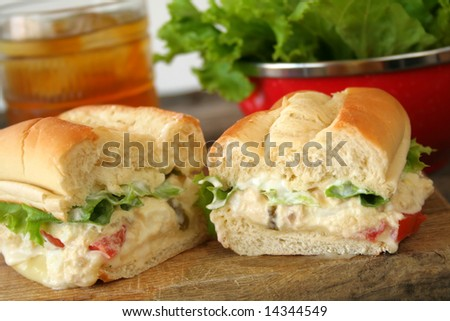 Fresh tuna salad sandwich on a hoagie roll with ice tea and a bowl of lettuce in the background. - stock photo
