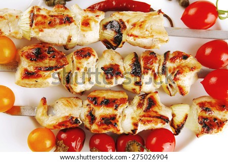 fresh turkey barbecue shish kebab served with tomatoes capers on platter isolated over white background - stock photo