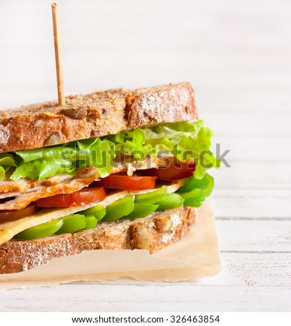 Fresh turkey sandwich with cheese and vegetables.