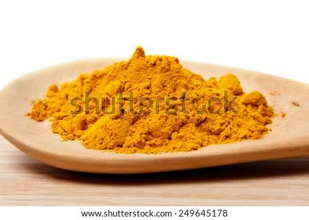Fresh  turmeric powder on wood background- shallow depth of field - stock photo