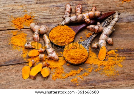 fresh turmeric roots on wooden table - stock photo