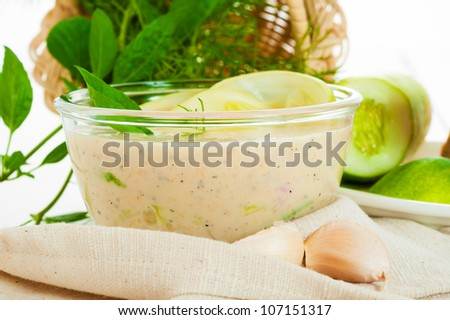 Fresh tzatziki in glass bowl with dill garlik and cucumber
