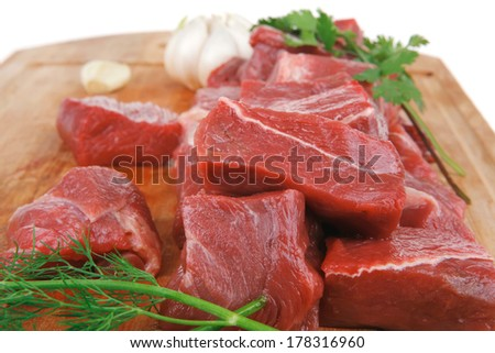 fresh uncooked beef meat slices over wooden cutting board ready to prepare with green hot and red peppers isolated over white background