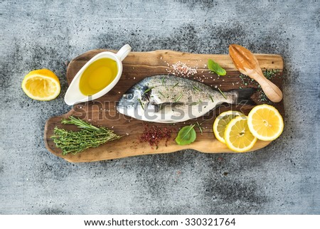 Fresh uncooked dorado or sea bream fish with lemon, herbs, oil and spices on rustic wooden board over grunge backdrop, top view - stock photo