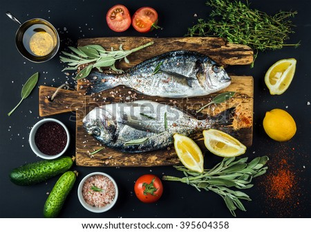 Fresh uncooked dorado or sea bream fish with lemon, herbs, oil, vegetables and spices on rustic wooden board over black backdrop, top view - stock photo