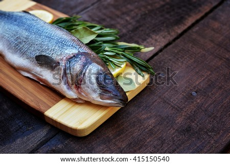 fresh uncooked  fish  with fresh herbs. fish with rosemary on wood. Piece of  fish with lemon on wooden background - stock photo