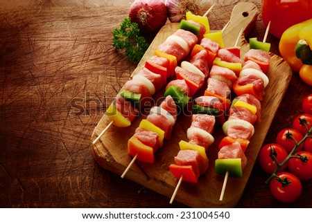 Fresh uncooked meat kebabs ready for grilling with colorful red, green and yellow sweet pepper, onion and tomato arranged on a wooden board in a rustic kitchen - stock photo
