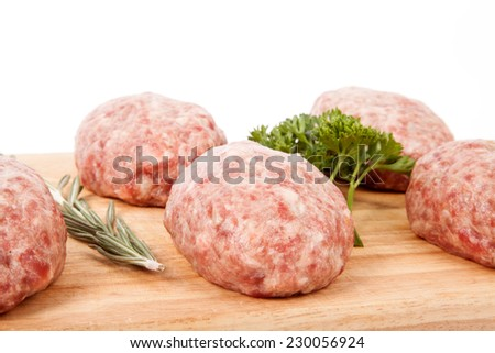 fresh uncooked patties on a wooden board with rosemary and parsley. Shallow depth of field - stock photo