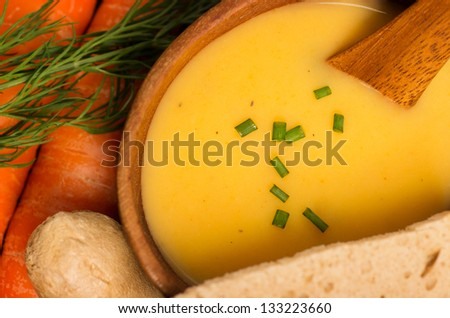 Fresh Vegan Carrot and Potato Soup surrounded by its ingredients - stock photo