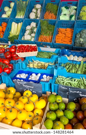 Fresh vegetable display at a greengrocer's shop in Europe with price tags in euros, no brand names - stock photo