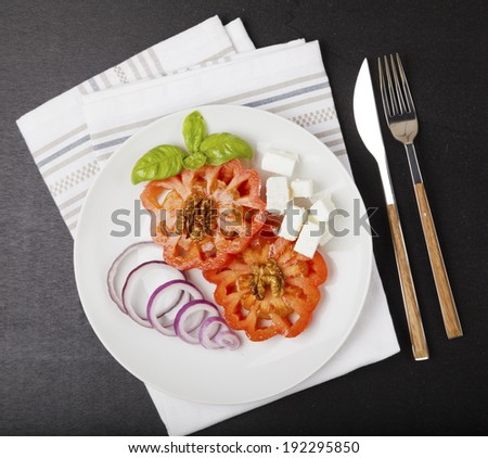 fresh vegetable greek salad. balsamic vinegar & olive oil. basil leaf. on a white plate and a dark background. cooking ingredients. salad ingredients - stock photo