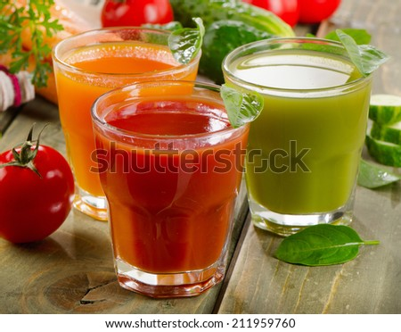 Fresh vegetable  juices on a wooden table. Selective focus