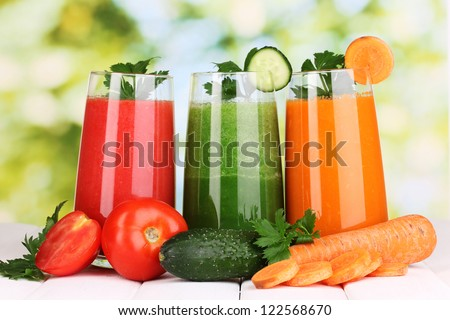 Fresh vegetable juices on wooden table, on green background - stock photo