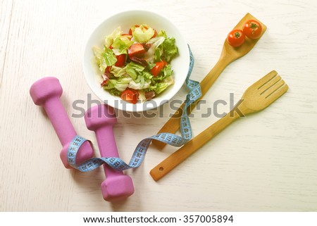 Fresh vegetable salad, dumbbells and measuring tape. Healthy food and diet concept - stock photo