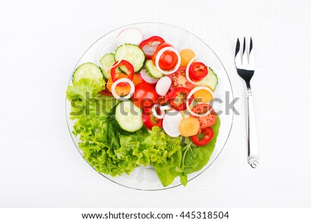 fresh vegetable salad in a glass dish with fork isolated on white - stock photo