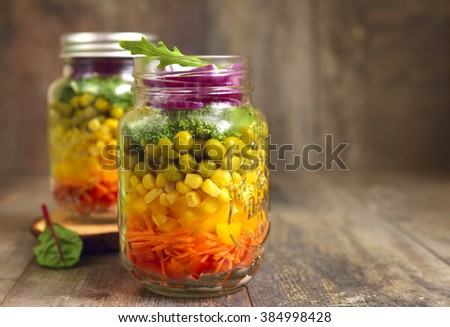 Fresh vegetable salad in a mason jar on an old wooden table.Rustic style. - stock photo