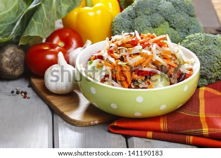 Fresh vegetable salad in green dotted bowl. Raw vegetables and fruits in the background.