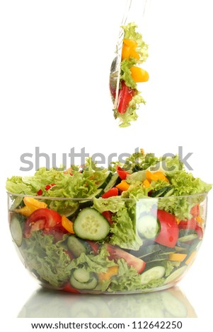 fresh vegetable salad in transparent bowl with spoon and fork isolated on white