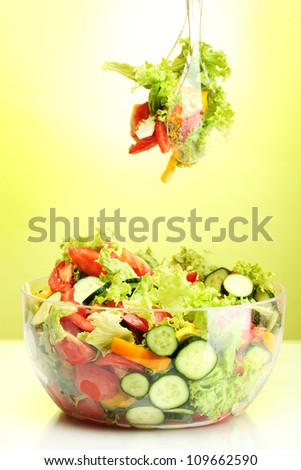 fresh vegetable salad in transparent bowl with spoon and fork on green background - stock photo