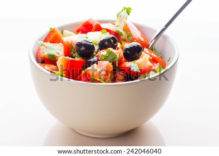 Fresh vegetable salad in white bowl isolated on white - stock photo
