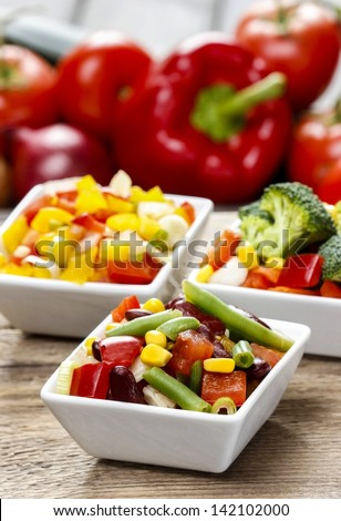 Fresh vegetable salad in white bowl. Spring party table. - stock photo