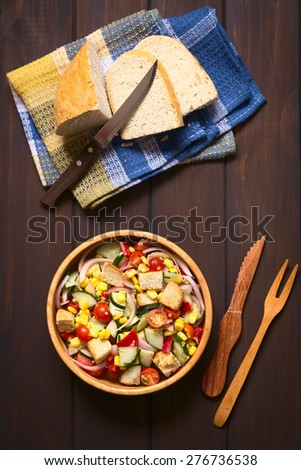 Fresh vegetable salad made of sweet corn, cherry tomato, cucumber, red onion, red pepper, chives with croutons in wooden bowl, photographed overhead on dark wood with natural light - stock photo