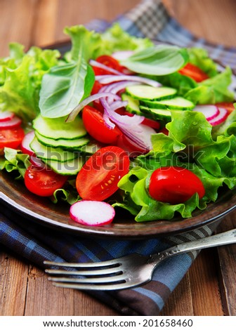 fresh vegetable salad on rustic wooden planks